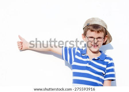 a little boy aged 6 to 8 years old with glasses and a cap showing a positive gesture.portrait - stock photo