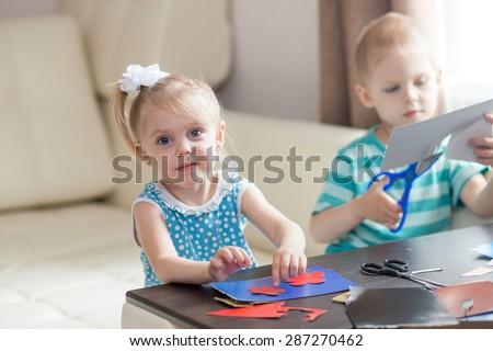 a little boy and a little girl cut from cardboard various details - stock photo