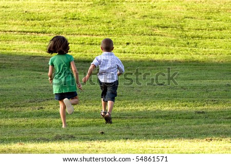 A little boy and girl run through the grassy field without a care in the world. - stock photo