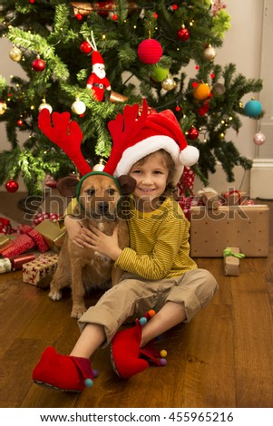 A little boy and his dog are sat cuddling in front of a Christmas Tree at home.  - stock photo