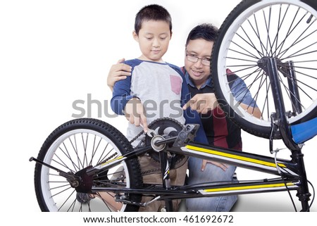 A little boy and his father using a wrench to repair a broken bicycle, isolated on white background