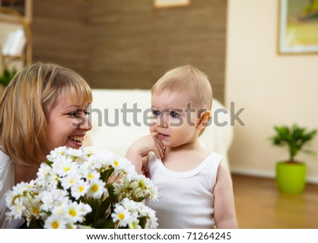 a little boy anf his mother playing with white flowers - stock photo