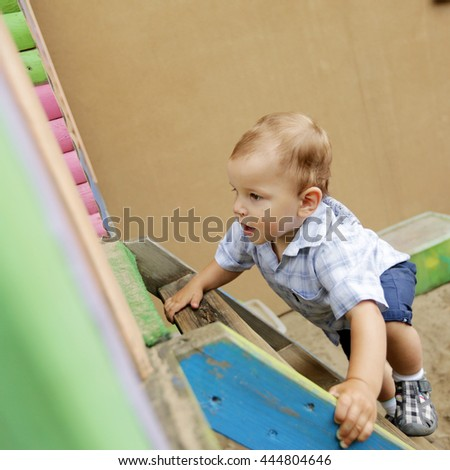 A little boy coming down the wooden stairs