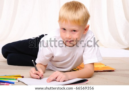 A little boy draws on the album with markers - stock photo