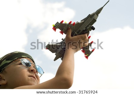 A little boy dreams of becoming a fighter pilot - stock photo
