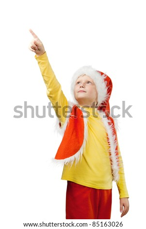 A little boy dressed as Santa Claus shows his finger on something at the top. Isolated on white background.