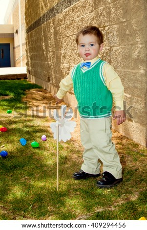 A little boy, dressed in his best on Easter looks at the camera with a messy face. - stock photo