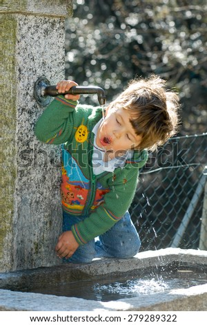 A little boy drinking from a water fountain in the park - stock photo