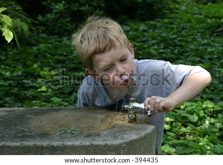 A little boy drinking from a water fountain in the park. - stock photo
