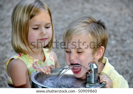 A little boy drinking water at a playground - stock photo