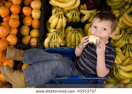 A little boy eating a delicious apple while surrounded by bananas.