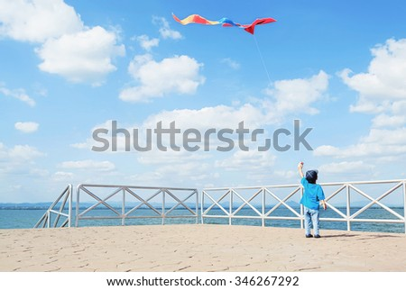 a little boy flying a kite on sea background