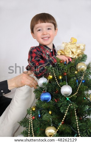 A little boy gets a boost to put an angel on top of a Christmas tree - stock photo