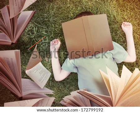 A little boy has fallen asleep on the grass with a brown book on his face. Open books and paper are flying up for an education or story concept. - stock photo