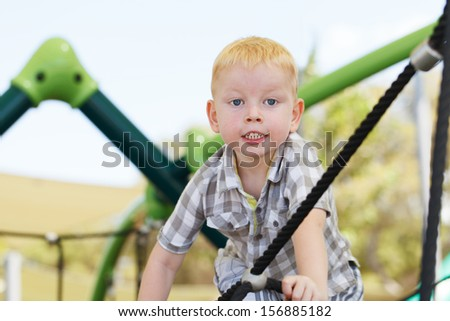 A little boy having a great time in a playground.