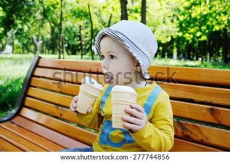 a little boy holding two ice creams. baby gray panama eating ice cream - stock photo
