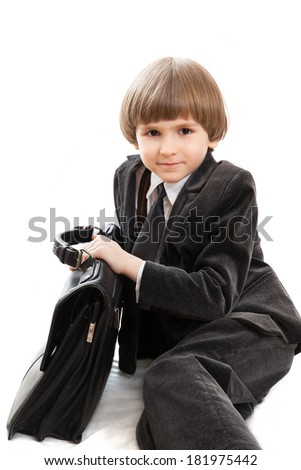 a little boy in a business suit with a leather briefcase
