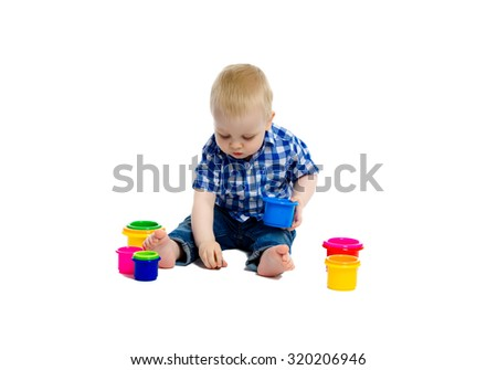 A little boy in checkered shirt plays on the floor. White background. Studio - stock photo