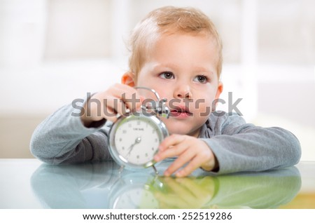 A little boy in the living room holding watercolors holding clock