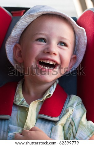 A little boy in white panama hat laughs in a children car seat - stock photo