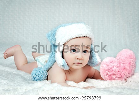 A little boy in winter hat with a heart in his hands. - stock photo