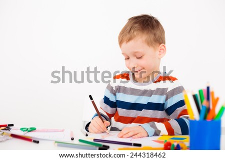 A little boy is happy to draw picture while sitting at his desk