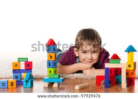 A little boy is lying on the floor near toys - stock photo