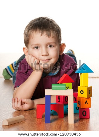 A little boy is lying on the floor near toys; on the white background - stock photo
