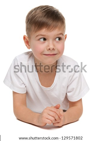 A little boy is lying on the floor on the white background and looking away