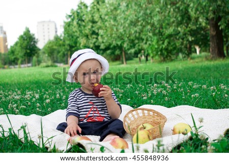 a little boy is sitting in the hat next to the basket of apples