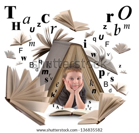 A little boy is under a big book on a white isolated background for an education or reading concept. There are letters floating around him. - stock photo