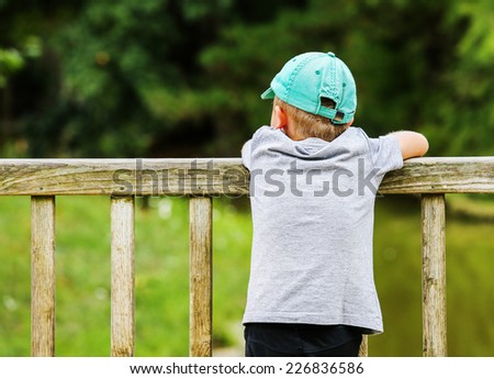 A little boy leaning over a wooden fence in the park