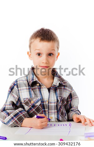 A little boy looking surprised while drawing a picture with a marker - stock photo