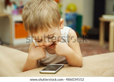 a little boy looking to smartphone lying on the couch at home