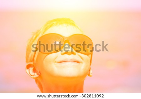A little boy on the beach looking through sunglasses on a bright sun and fun. Family composition
