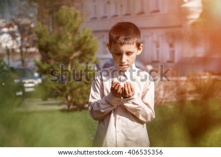 A little boy praying outdoor in nature - stock photo