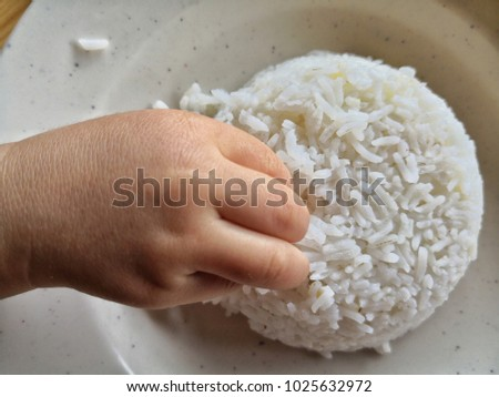 a little boy's hand taking the rice