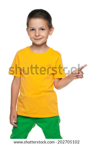 A little boy shows his finger to the side against the white background - stock photo