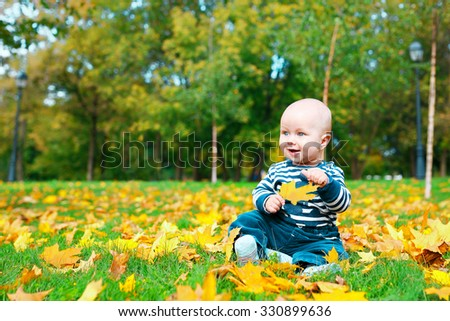 A little boy sits among autumn leaves