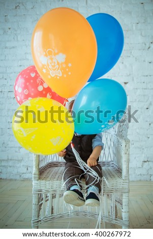 A little boy sits on a white wicker chair in the studio and holding a five bright multicolored balloons. First Birthday. Childhood - stock photo