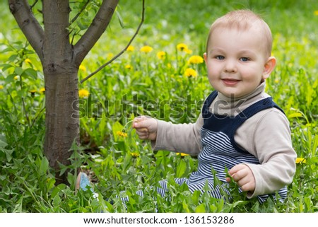A little boy sitting on the grass playing and smiling. - stock photo