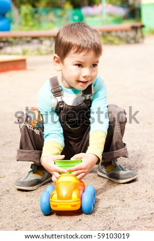 a little boy smiling and playing in the toy car in the children's village on a summer day - stock photo