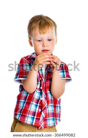 A little boy stands and examines small toy - stock photo