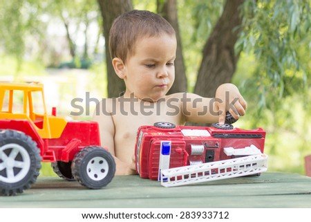 a little boy, two years old, smiling, summer, naked to the waist, sitting at a table playing with a red fire engine and a red tractor