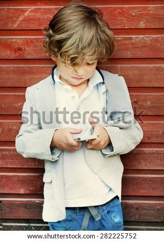 A little boy using a phone - stock photo