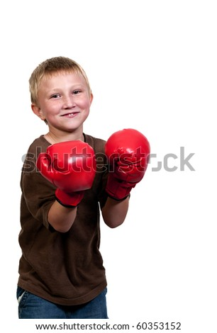 A little boy wearing a pair of boxing gloves - stock photo