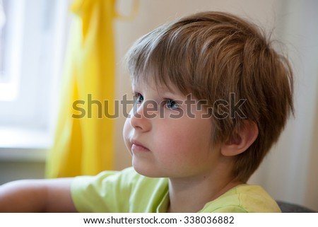 a little boy who looks and listens attentively - stock photo