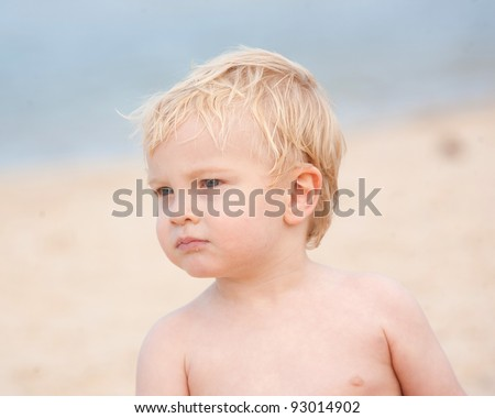 A little boy with a serious expression on the beach glances sideways.