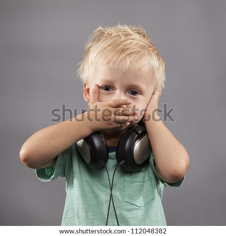 A LIttle Boy with headphones holds hands over ears and mouth. - stock photo