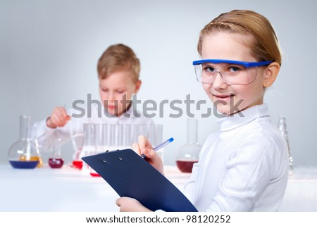 A little boy working with liquid with his assistant making notes at foreground - stock photo